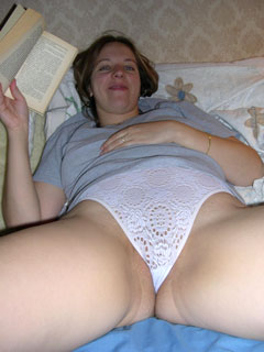 Married woman reading book on family bed